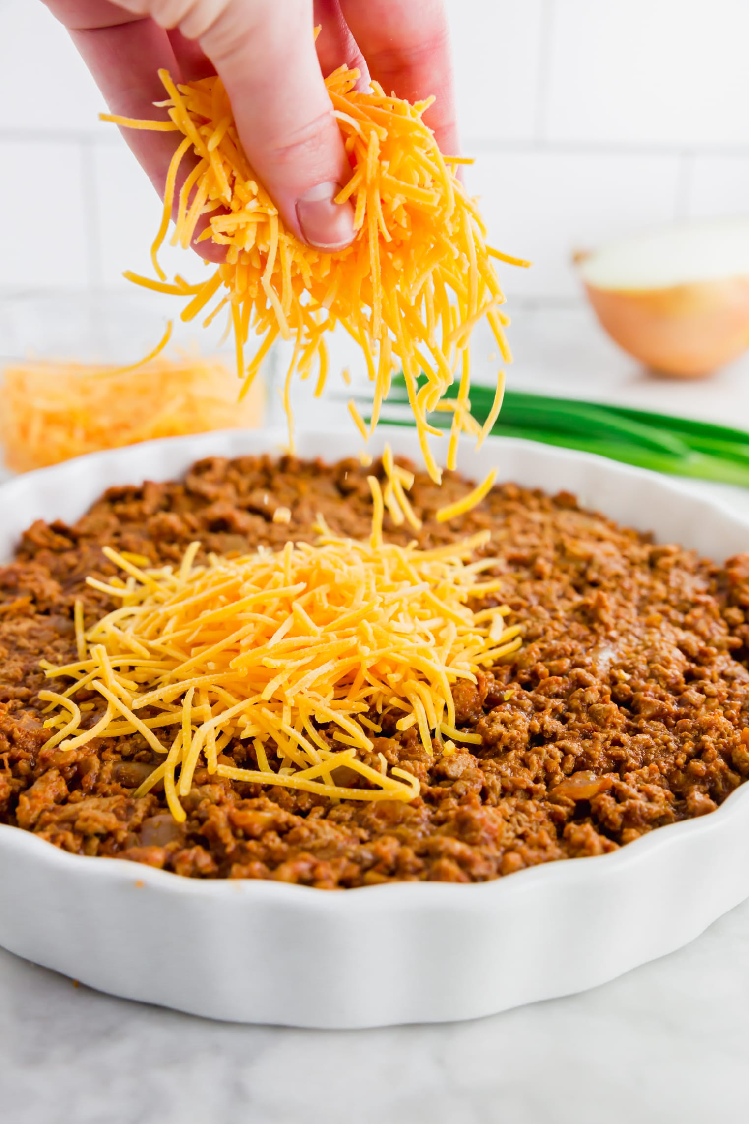 A photo of shredded cheddar cheese being sprinkled over turkey chili for gluten-free chili dip.