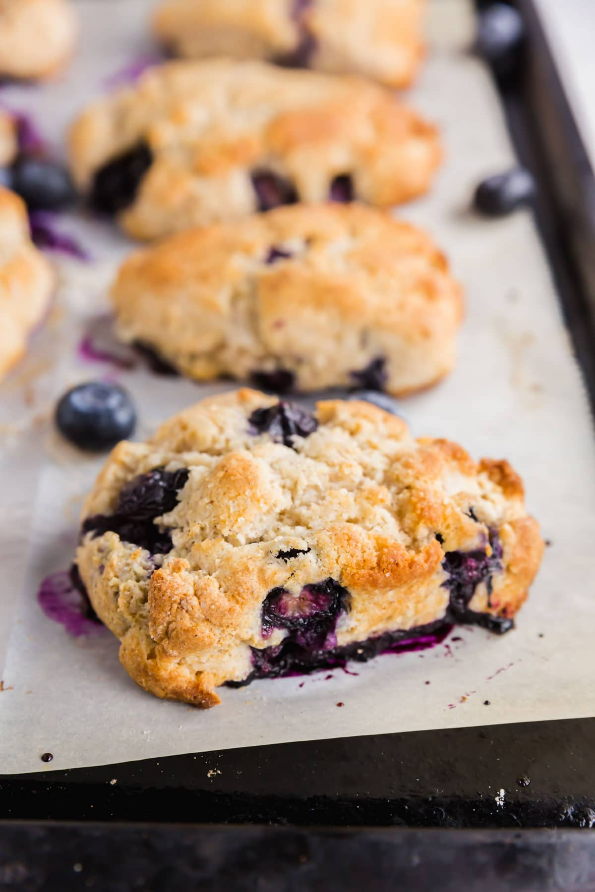 A baking sheet with gluten-free blueberry scones fresh from the oven.