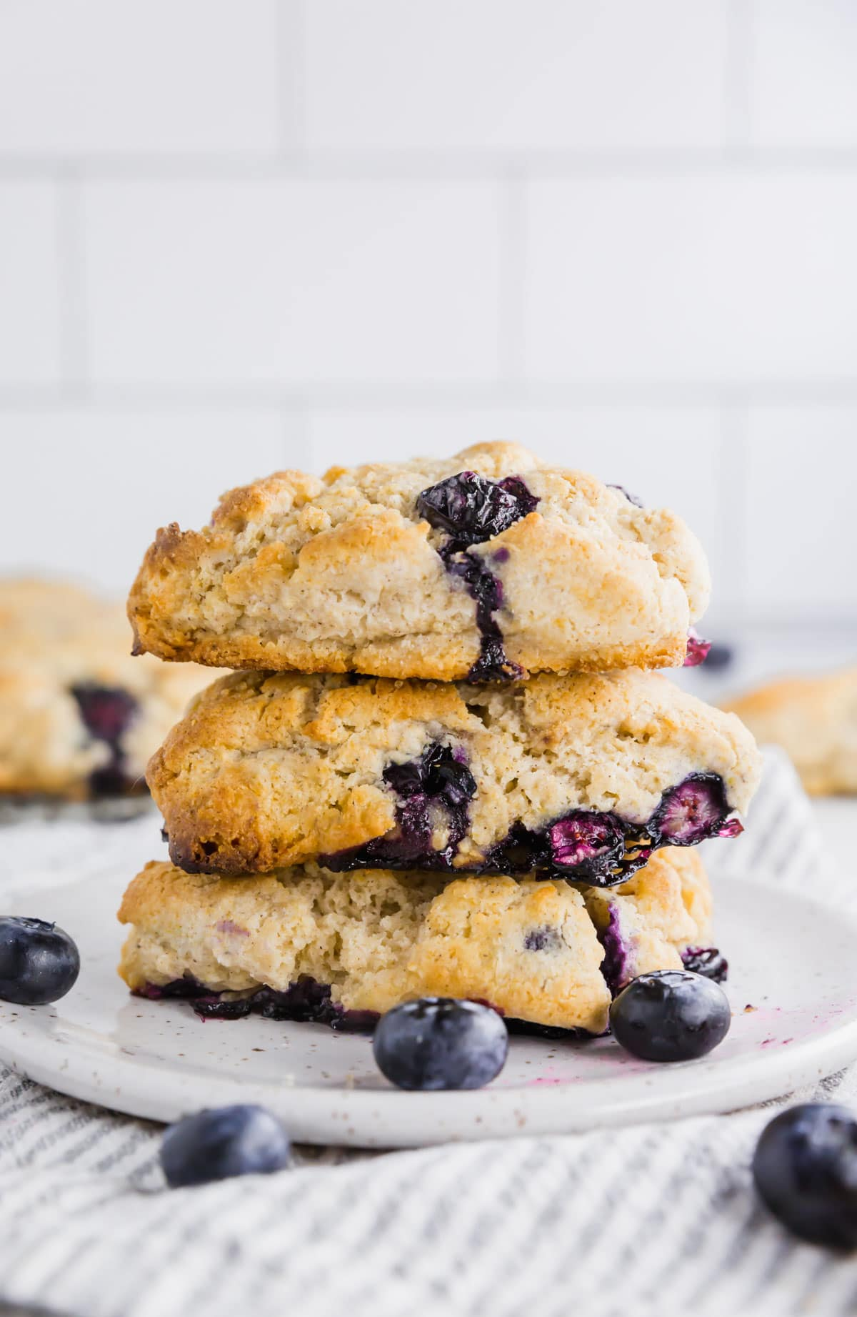 A stack of three gluten-free blueberry scones on a small plate.