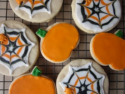 A cooling rack with orange and black spider web and pumpkin decorated sugar cookies.