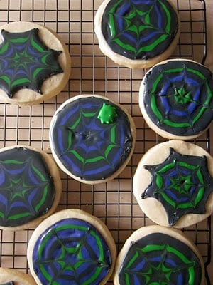 A cooling rack with black, purple and green spider web decorated sugar cookies.