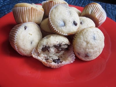 A pile of mini chocolate chip muffins on a red plate.