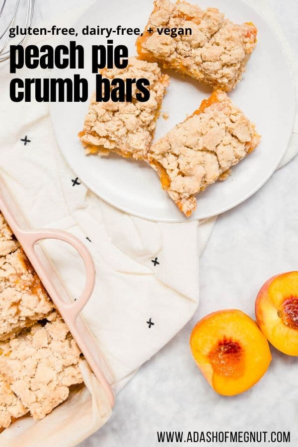 An aerial view of peach pie crumb bars on a plate with fresh peaches next to it.