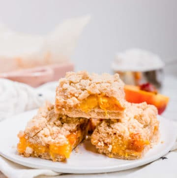 A view of three peach crumb bars in a stack on a plate.