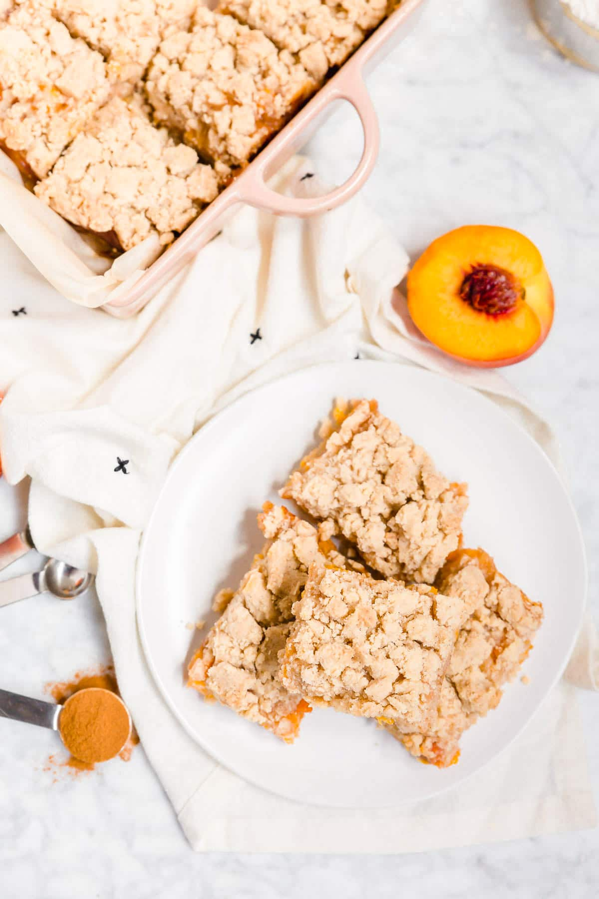 An aerial view of peach crumb bars on a plate with fresh peaches next to it.