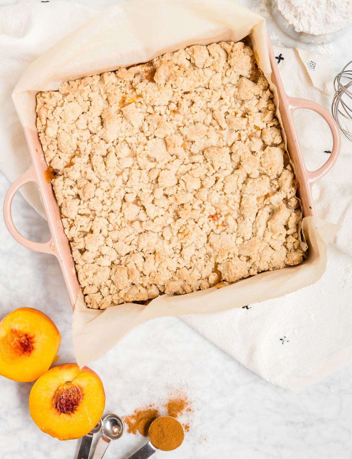 An aerial view of a baking dish with gluten-free vegan peach crumb bars in it and fresh peaches next to it.