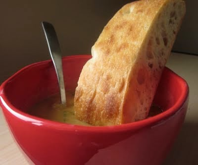 Broccoli cheddar soup in a red bowl with a spoon and gluten-free ciabatta bread.