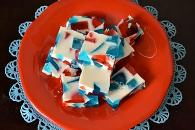 Stain glass jello shots that are white, red and blue on a red plate.