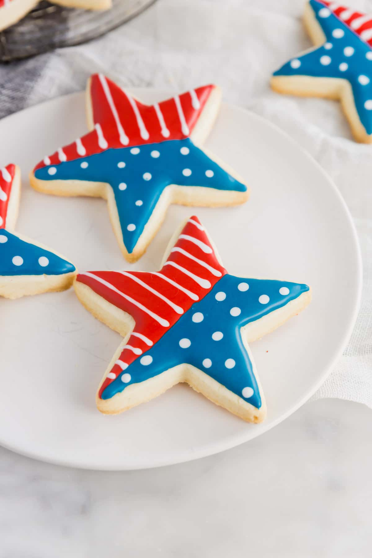An aerial photo of a white plate with star shaped sugar cookies with a flag design on them.