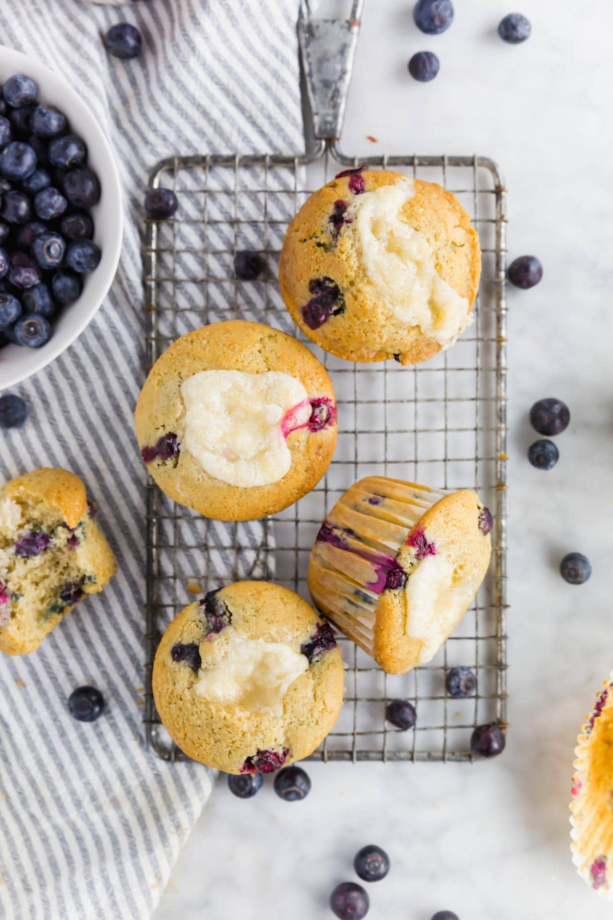An overhead photo of gluten-free blueberry cream cheese muffins on a wire cooling rack with fresh blueberries surrounding them.