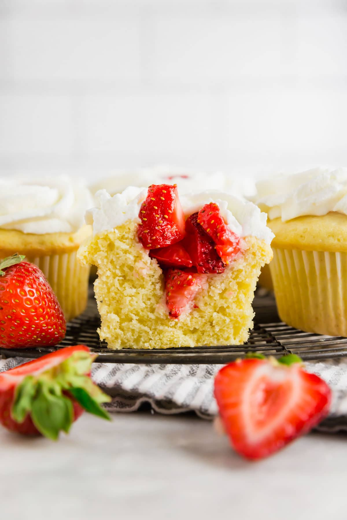 A strawberry shortcake cupcake sliced in half to show the strawberry filling on top of a wire cooling rack.