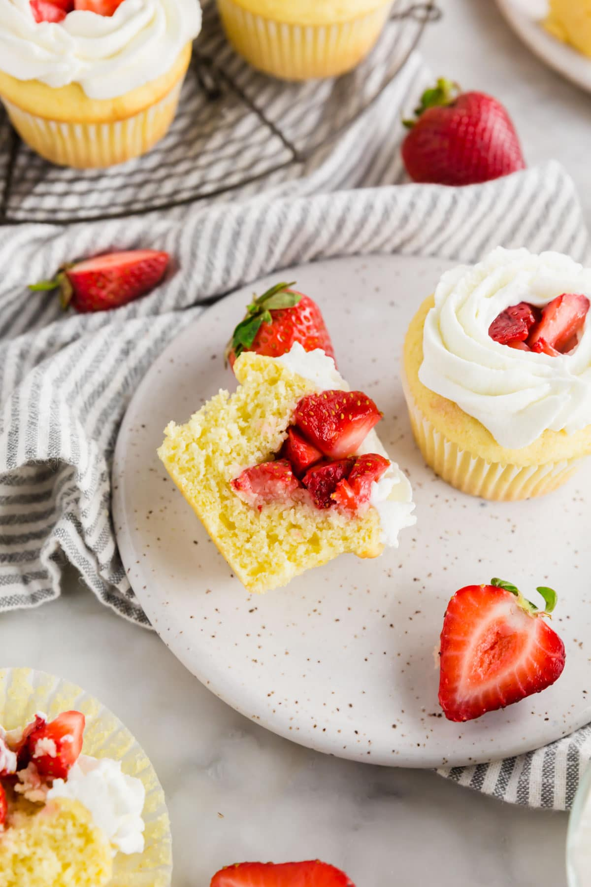Strawberry shortcake cupcakes on a plate with one sliced in half and fresh strawberries surrounding the plate.
