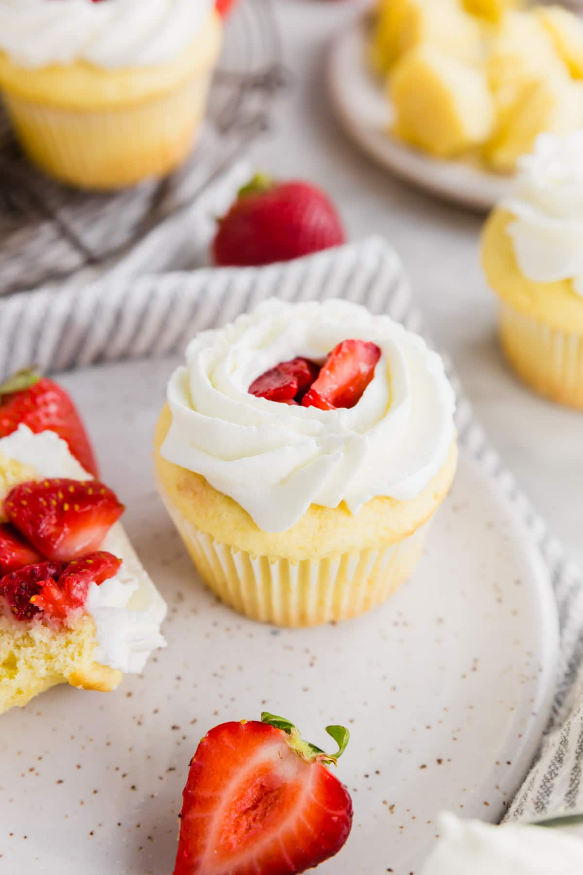 A photo of a strawberry shortcake cupcake topped with fresh whipped cream on a plate.