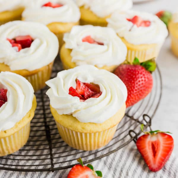 A wire cooling rack with gluten-free strawberry shortcake cupcakes on it topped with fresh whipped cream.