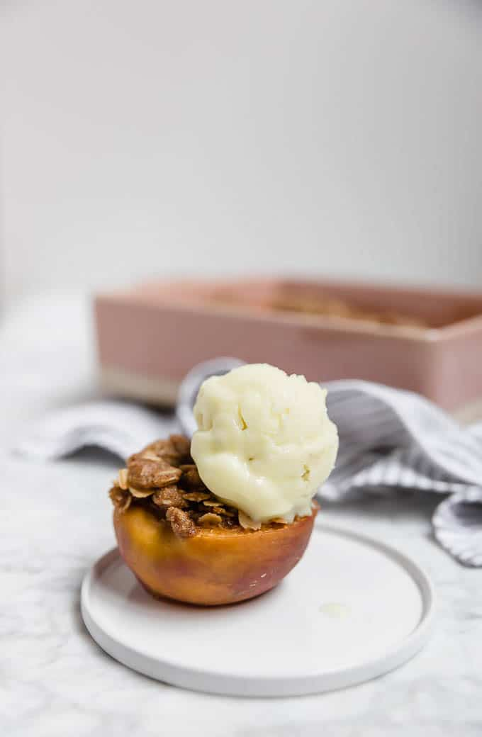 Straight on view of a peach on a plate stuffed with streusel topping and a scoop of ice cream with a pink baking dish in the background.