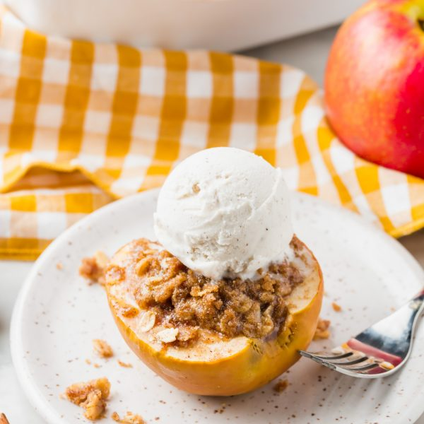 A photo of baked apple topped with ice cream and gluten-free streusel on a plate.