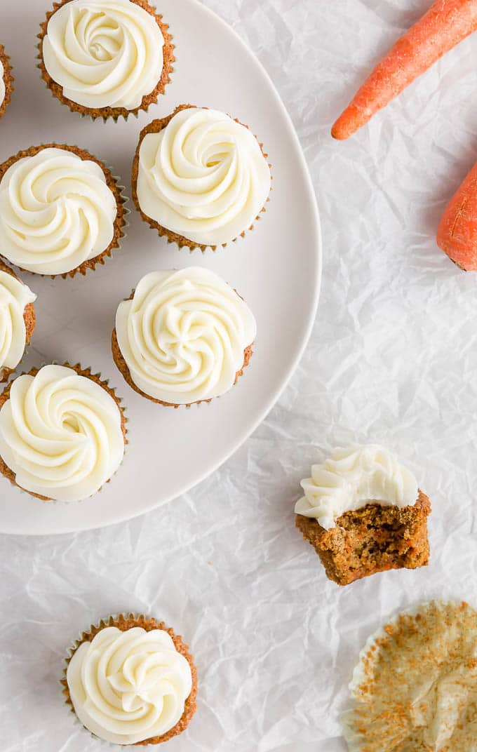 A platter of gluten free carrot cake cupcakes with cream cheese frosting.