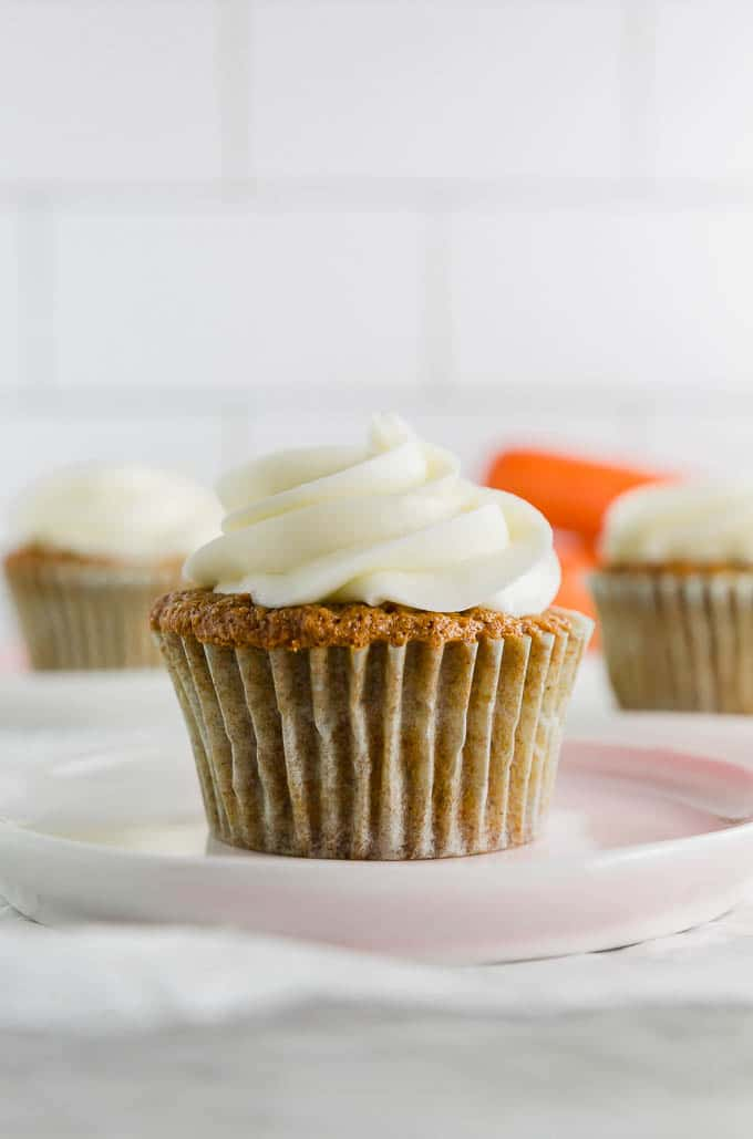A photo of a gluten free carrot cake cupcake with cream cheese frosting on a plate with carrots in the background.