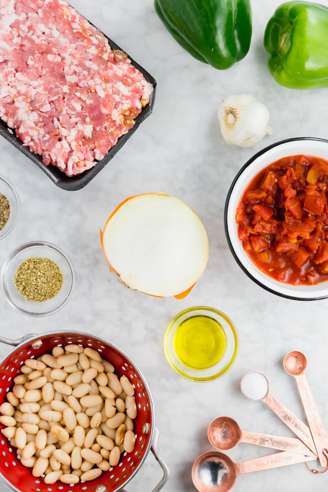 A photo of raw italian sausage, crushed tomatoes, onion, beans, olive oil, herbs, spices, and garlic ready to make white bean italian sausage stew.
