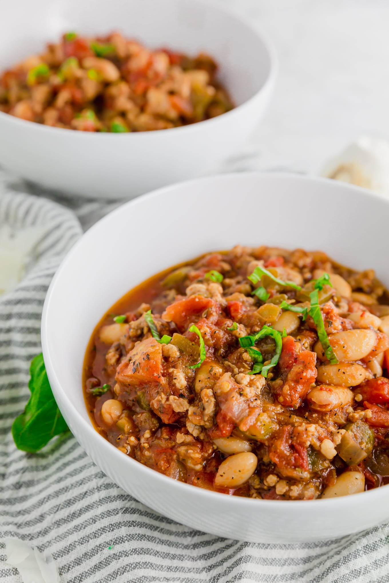 A photo of two bowls of italian sausage stew with white beans topped with fresh basil.