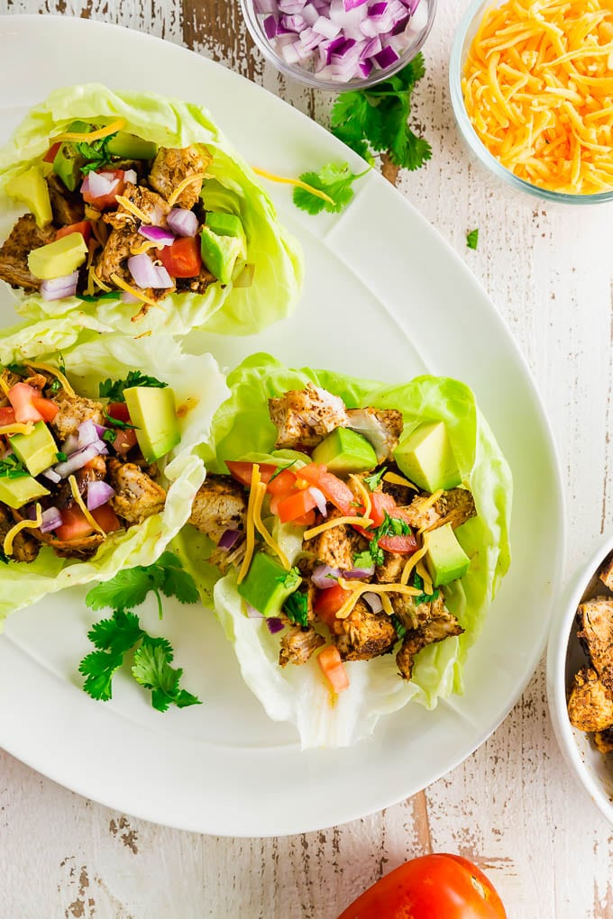 A plate with three chicken taco lettuce wraps with cilantro and ingredients surrounding the plate.