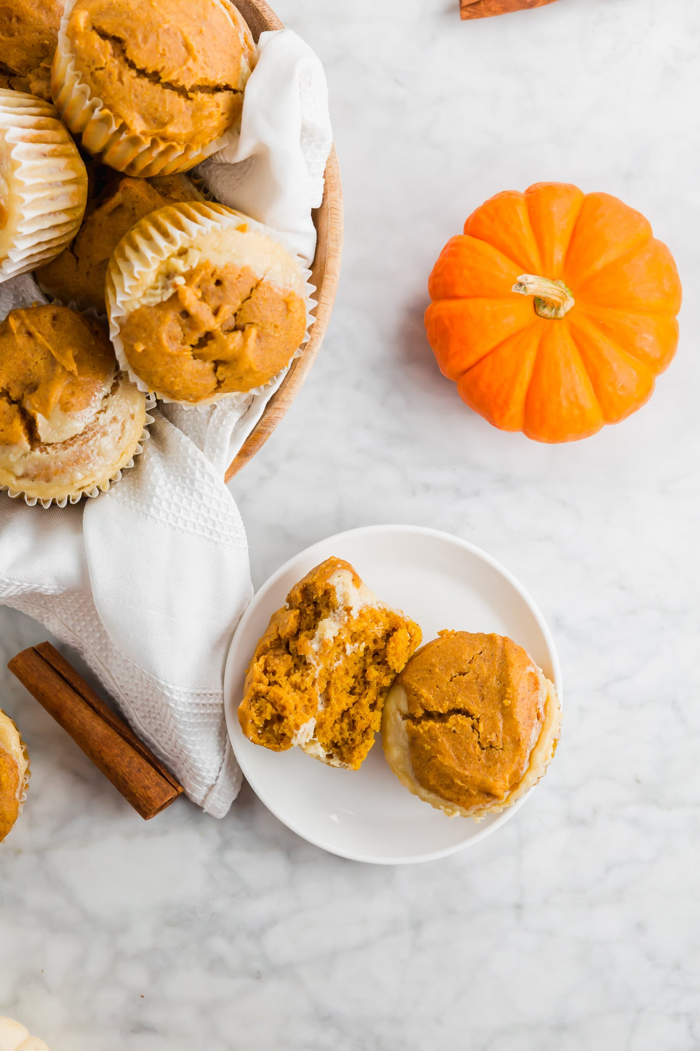A photo of a pumpkin cheesecake muffin split in half on a plate.