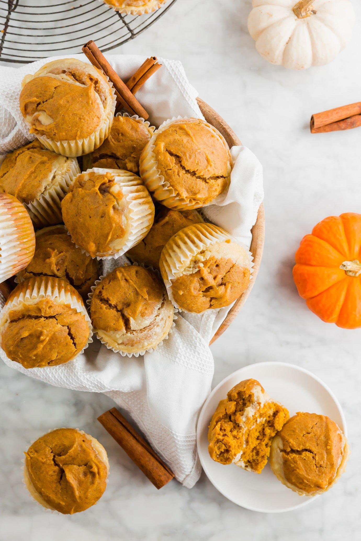 A basket of gluten-free pumpkin cream cheese muffins with fresh pumpkins and cinnamon sticks.