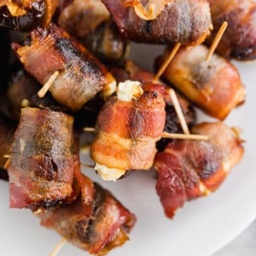 A photo of 3-ingredient bacon wrapped dates with goat cheese with toothpicks inserted in the center on a platter.