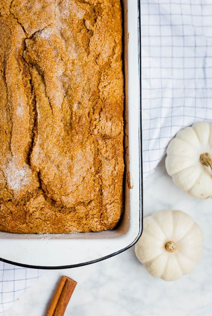A white loaf pan with gluten-free dairy-free pumpkin bread and white mini pumpkins and a cinnamon stick.