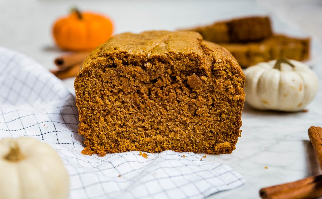 A loaf of gluten-free pumpkin bread with fresh pumpkin and cinnamon sticks.