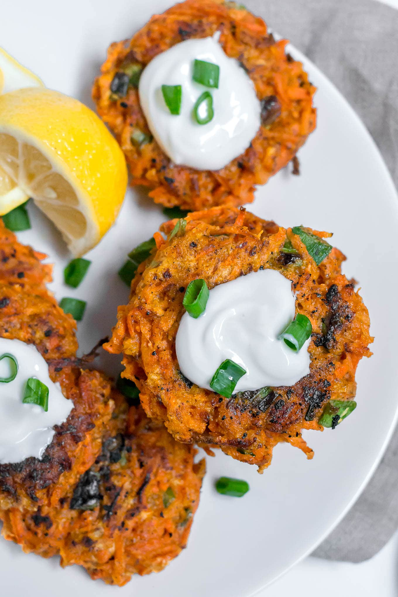 An aerial view of gluten-free carrot fritters on a white plate topped with greek yogurt, and green onions with a lemon wedge.