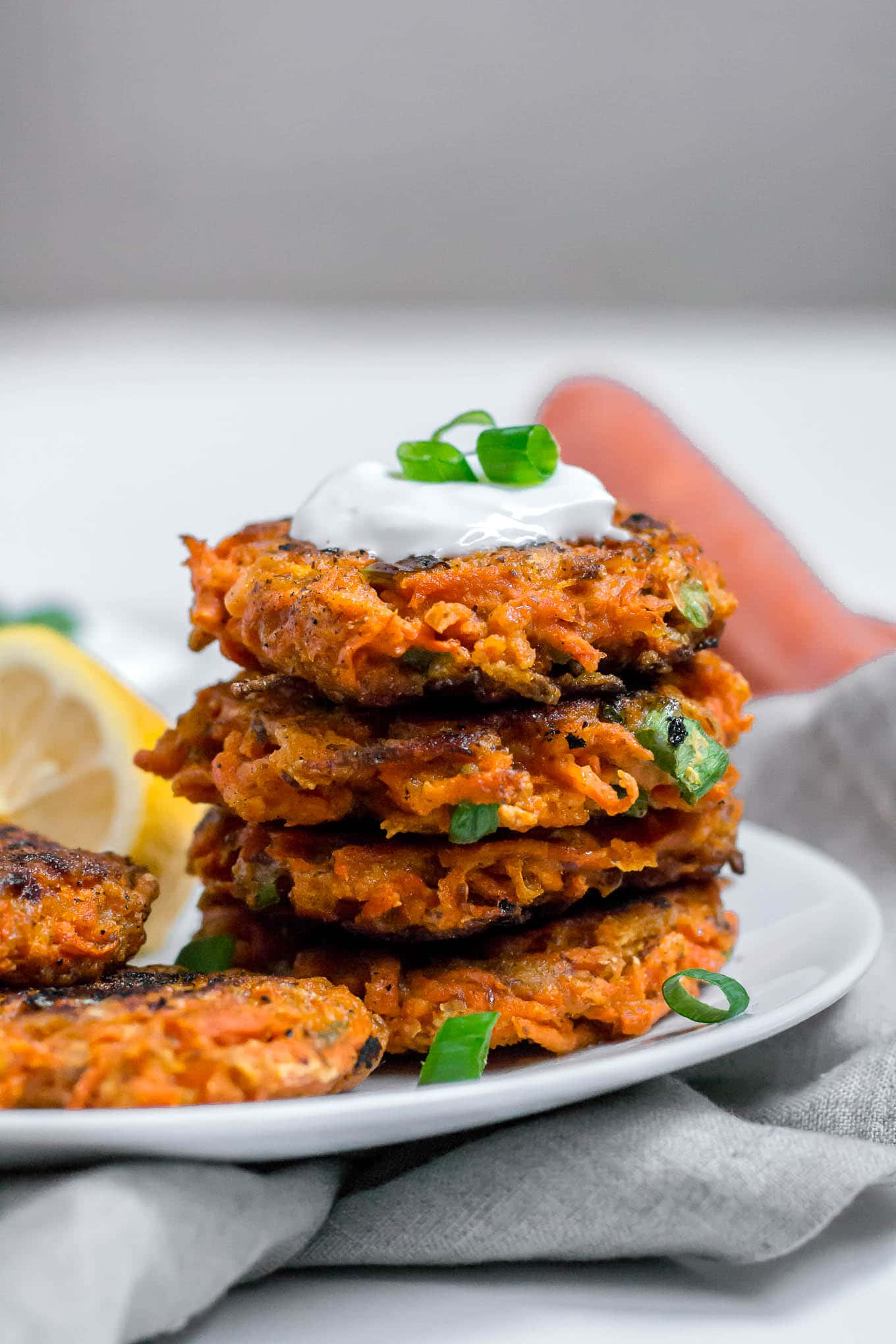 A straight on shot of a stack of gluten-free carrot fritters topped with greek yogurt and green onion with a lemon wedge off to the side on a white plate with gray napkin.