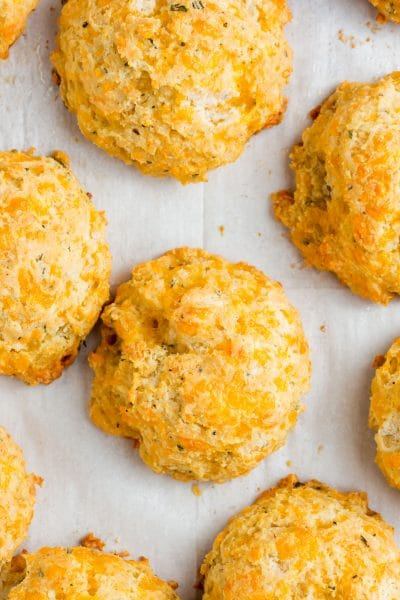 An overhead shot of gluten-free cheese biscuits on parchment paper.