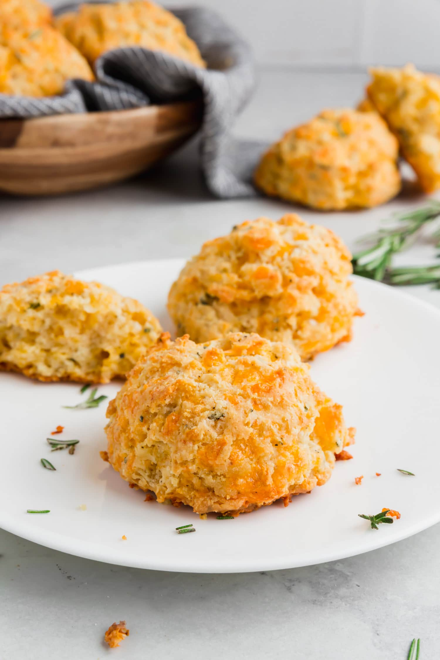 A photo of gluten-free cheese biscuits on a plate with fresh rosemary and a basket of biscuits in the background.