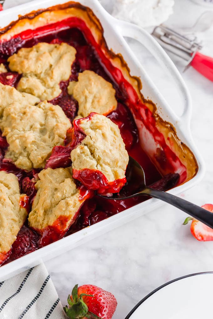 A photo of a baking sheet with strawberry cobbler topped with a spoon scooping out gluten free vegan biscuits.