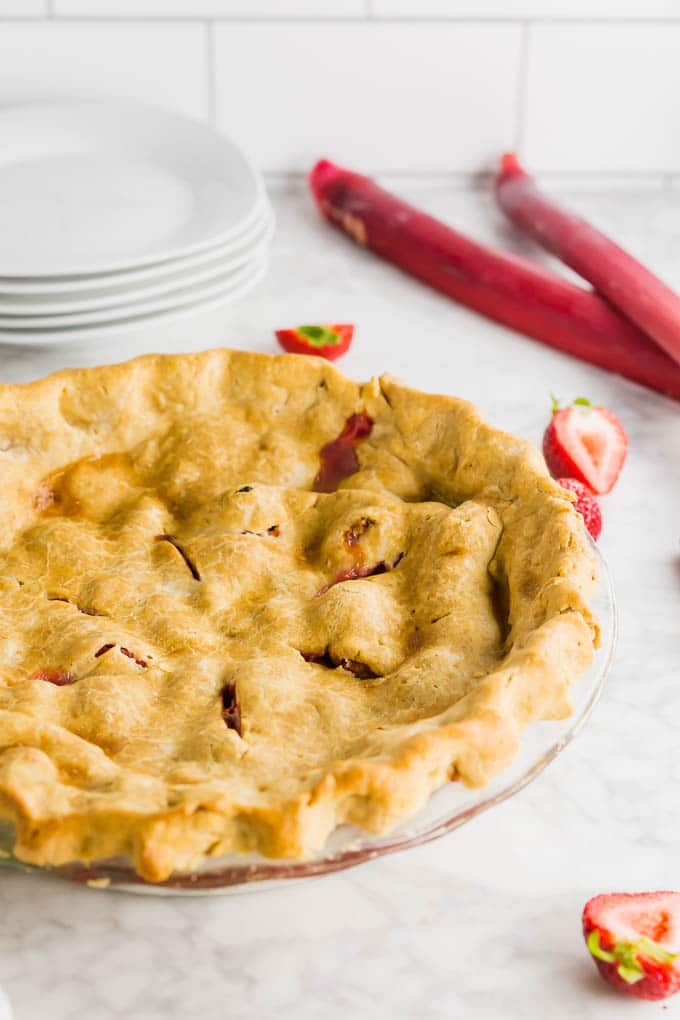 A gluten free rhubarb strawberry pie with a golden brown crust straight from the oven with a stack of plates.