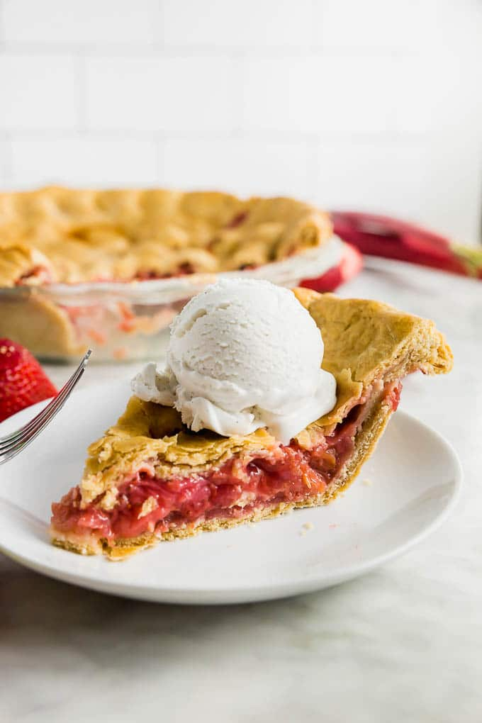 A piece of strawberry rhubarb pie on a plate topped with a scoop of vanilla ice cream.