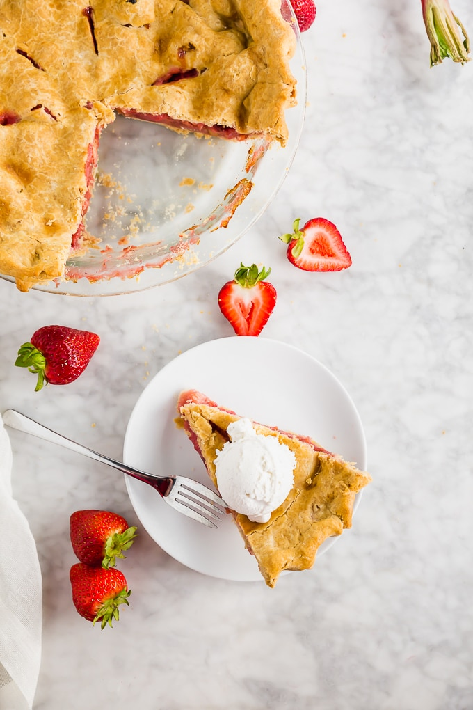 A piece of rhubarb strawberry pie on a plate with a fork and a larger gluten free pie.