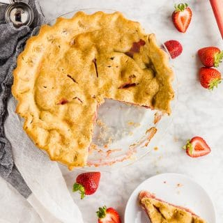 A photo of a gluten free strawberry rhubarb pie with a slice cut out of the whole pie and placed on a plate with a fork.
