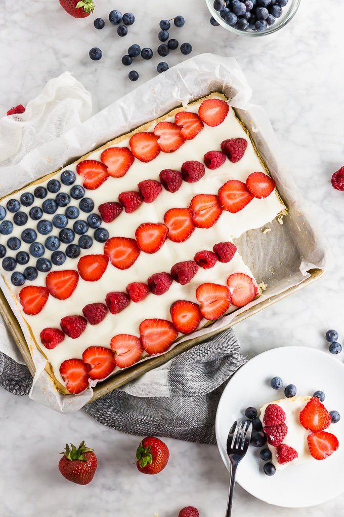 A gluten free sugar cookie dessert pizza decorated like the American Flag with cream cheese frosting, blueberries, raspberries and strawberries.