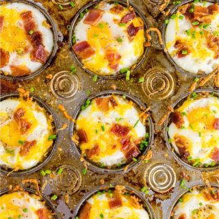 A photo of a muffin tin filled with gluten free hash brown breakfast egg cups topped with bacon, chives and cheddar cheese.