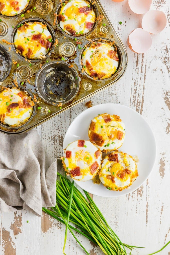 A photo of a muffin tin filled with hash brown egg cups with three egg cups on a plate with a bunch of chives.
