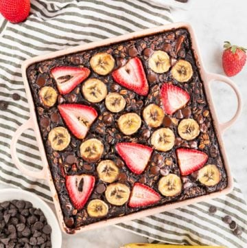 A photo of a baking dish with chocolate strawberry banana baked oatmeal in it with sliced bananas and strawberries on top and a bowl of chocolate chips next to it.