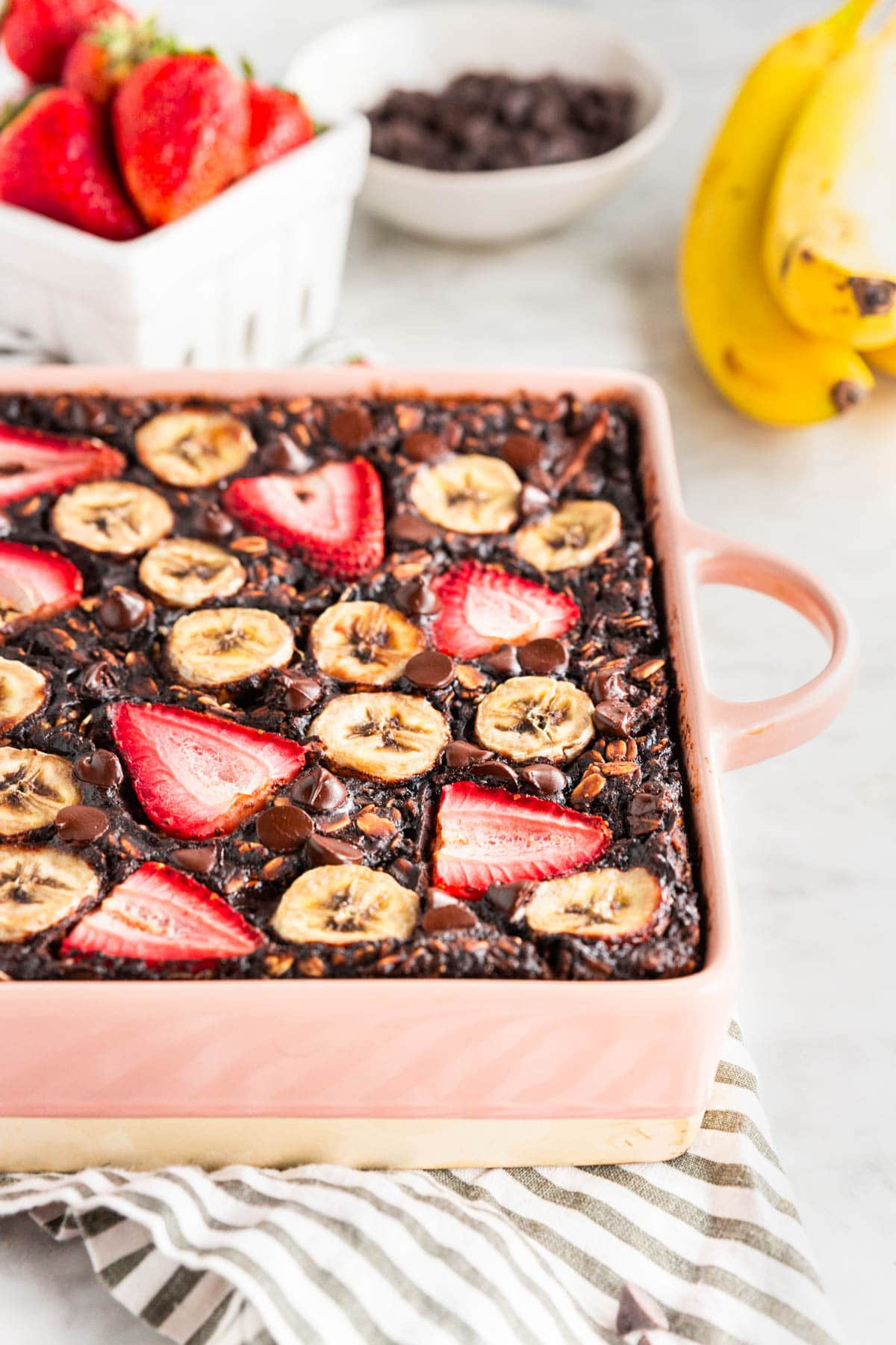 A photo of a pink baking dish with chocolate baked oatmeal topped with sliced bananas and strawberries on top.