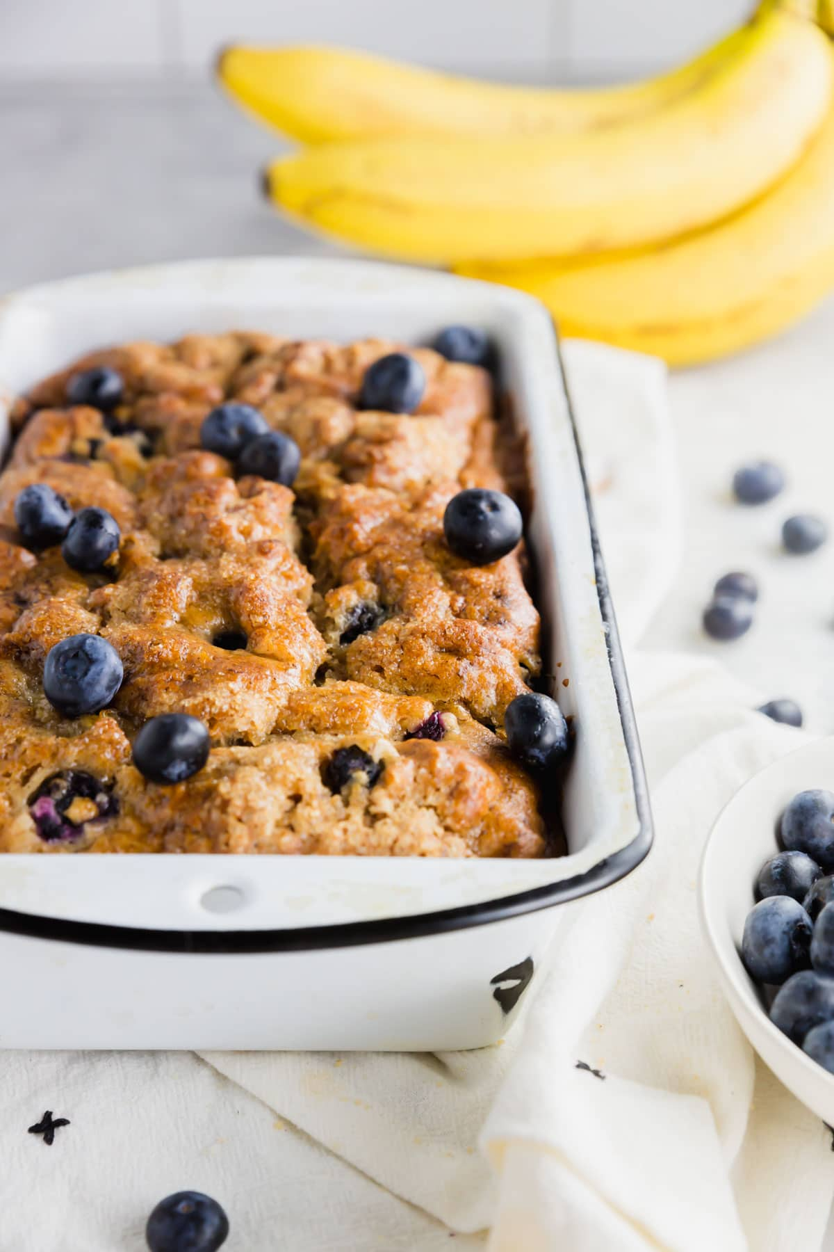 A photo of a gluten-free vegan blueberry banana bread in a white loaf pan with bananas in the background.