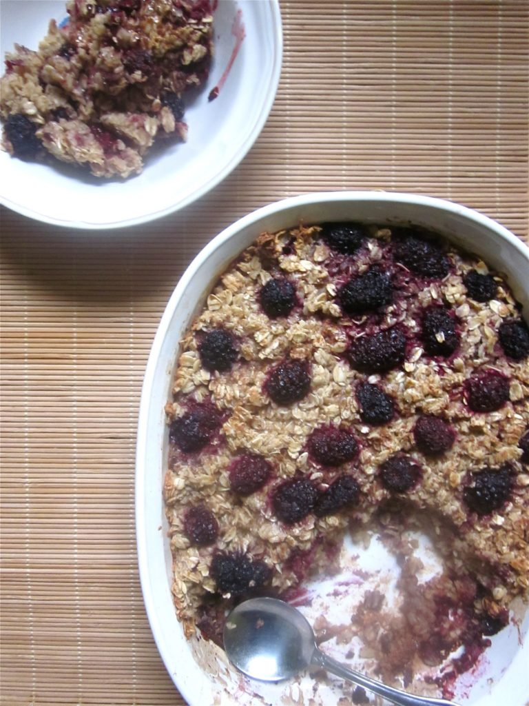 A casserole dish of blackberry baked oatmeal with a spoon.
