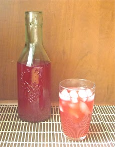 A glass of passion iced tea lemonade with a carafe behind it.
