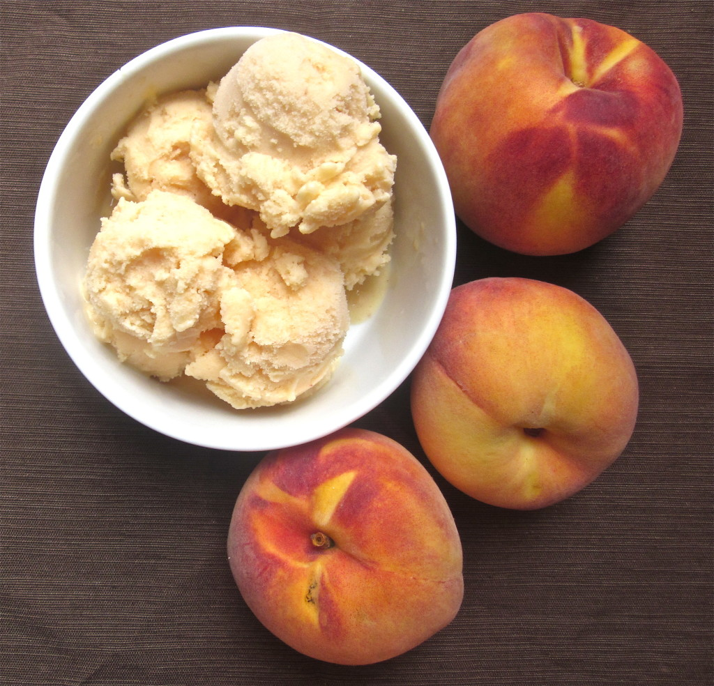 A bowl of peach frozen yogurt with fresh peaches on the side.