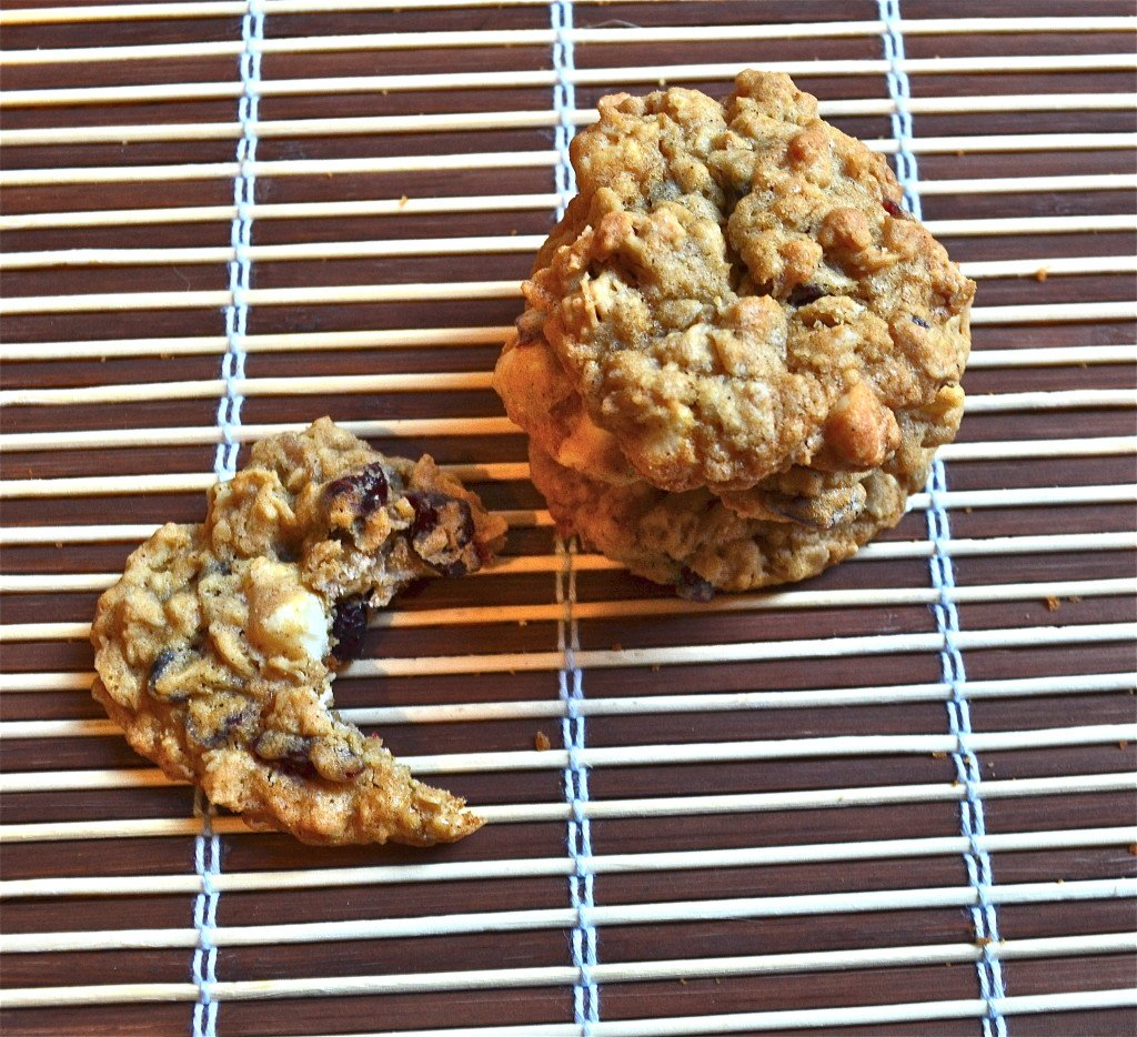 A stack of white chocolate cranberry oatmeal cookies with a cookie on the side with a bite taken out of it.