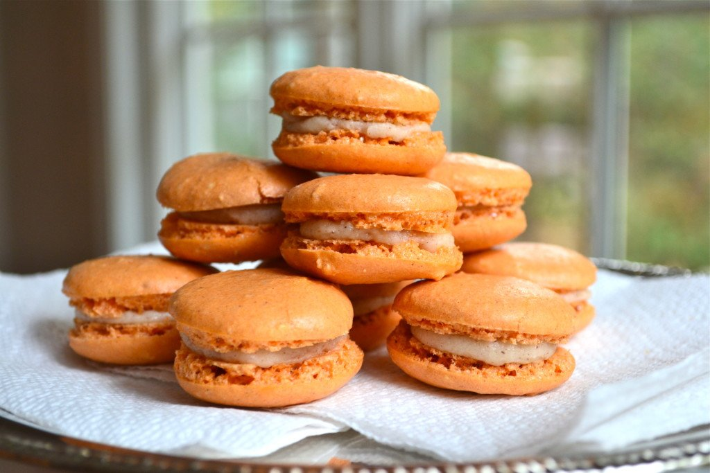 A stack of pumpkin pie macarons filled with cream cheese frosting.